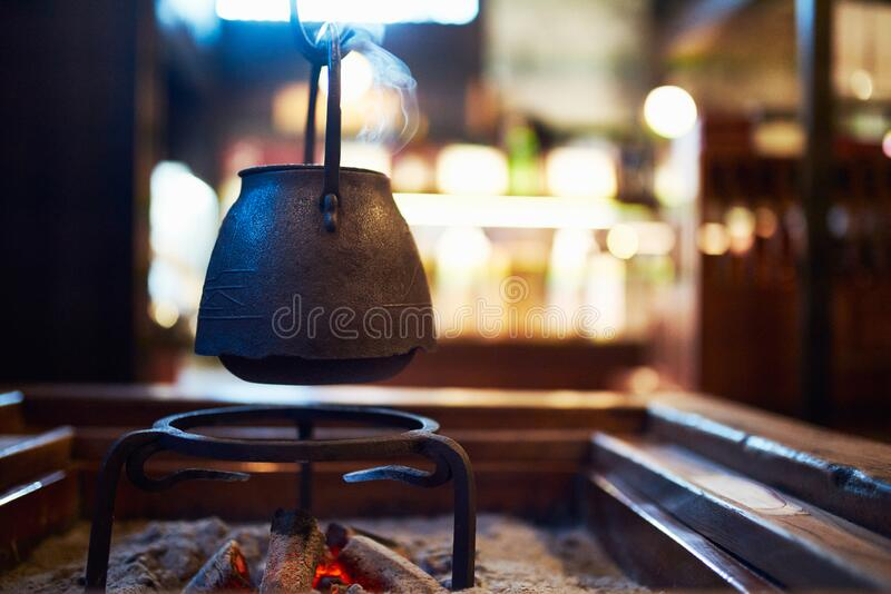 Tetsubin Cast Iron Kettle Suspended Over an Irori Hearth in a traditional Japanese style Farm House Heated over Charcoal stock photography