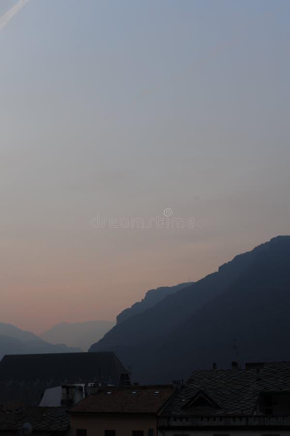 Tetti della città del San Vincenzo in d'Aosta della valle d'Aosta Valle in Italia con le alpi italiane nell'inverno al crepusco immagini stock libere da diritti