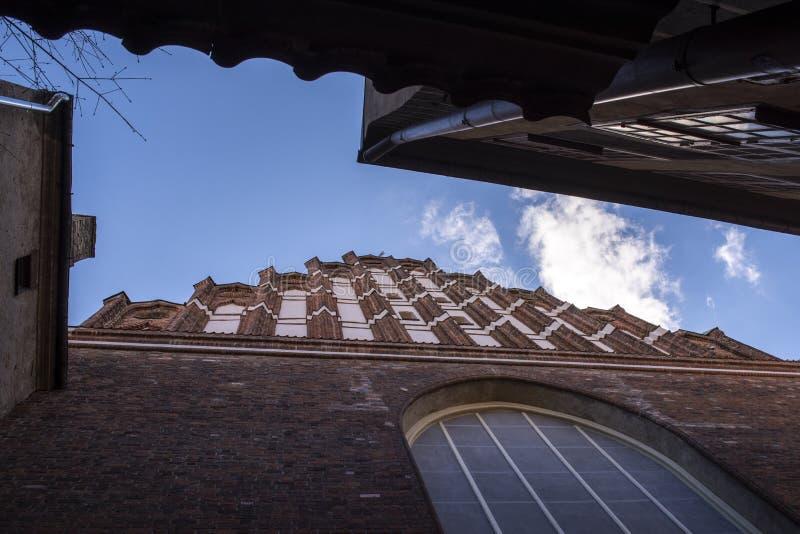 Tetti di vecchie case e cielo blu sopra la città immagine stock