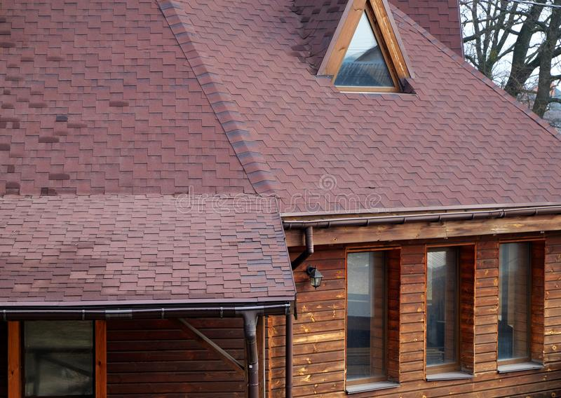 Tetto Asphalt Shingles e finestra della mansarda della soffitta Costruzione del tetto Riparazione di tetto Grondaia della pioggia immagine stock libera da diritti