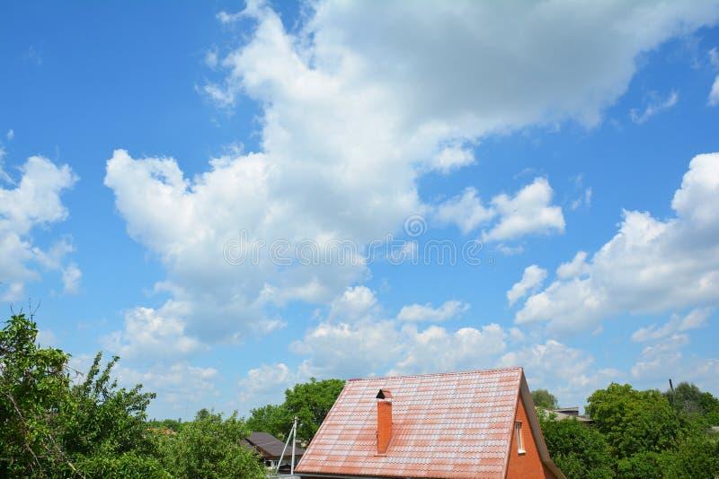 Tetto di mattoni con tetto di acciaio e splendide nuvole di cielo blu immagini stock