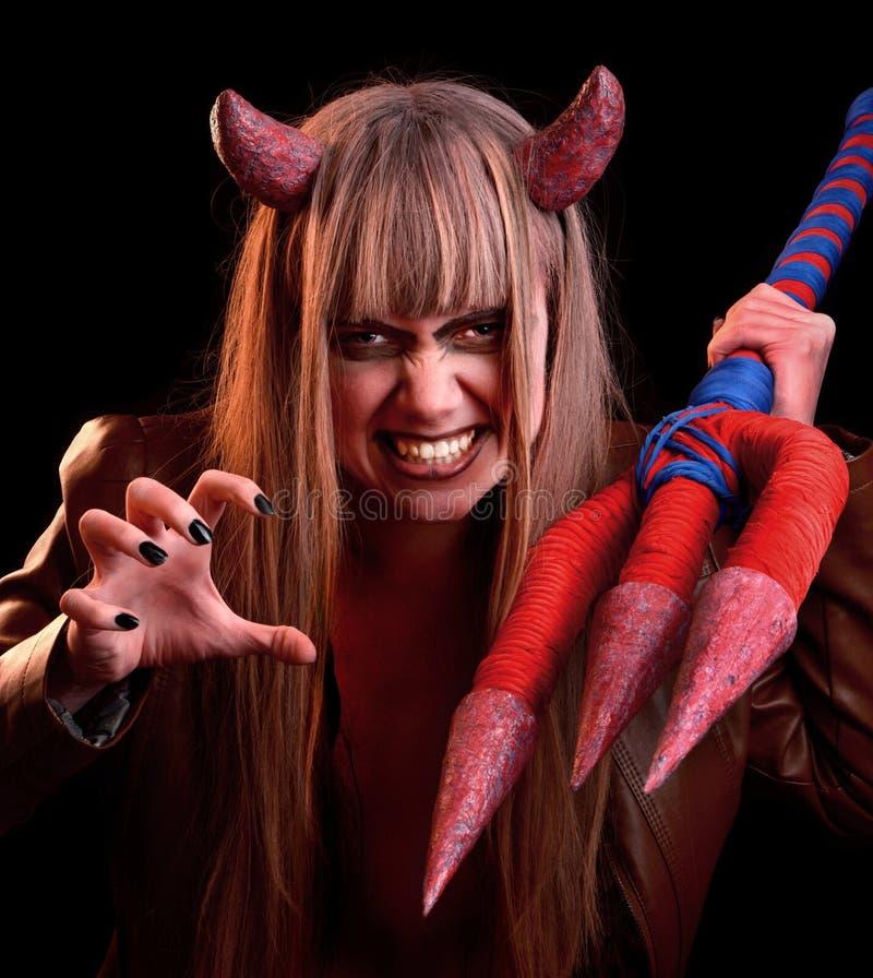 Teufelmädchen mit einem Dreizack auf einem schwarzen Hintergrund stockfotos
