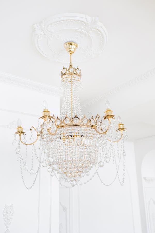 Teurer Innenraum Großer elektrischer Leuchter hergestellt von den transparenten Glasperlen Weiße Decke verziert mit Stuck lizenzfreie stockbilder