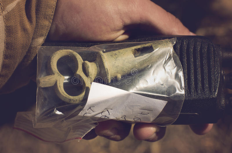 Teutonic, historical, old bung in a plastic bag in man hand. Metal detecting hobby. stock image