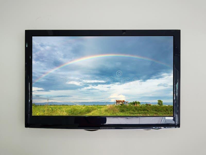 Tevê conduzida no fundo da parede com o arco-íris no céu foto de stock royalty free