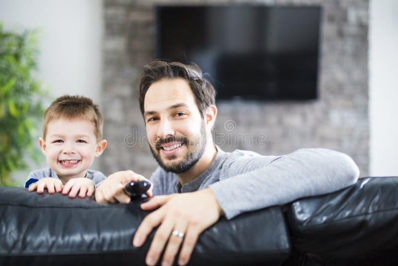 Tevê de And Children On Sofa At Home Watching do pai junto foto de stock