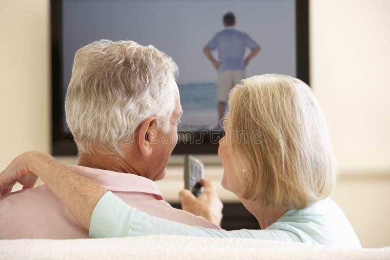 Tevê de observação do tela panorâmico dos pares superiores em casa fotos de stock