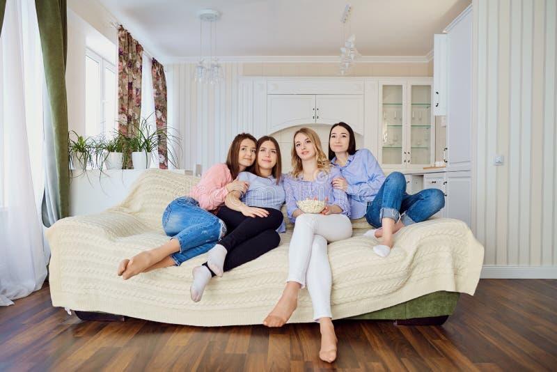 Tevê do relógio das amigas que senta-se no sofá foto de stock
