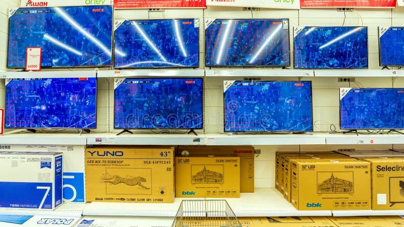 Tevês para a venda em um grande supermercado Texto no russo: Auchan, fósforo fotos de stock