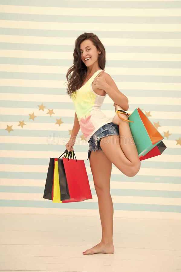 Teveel pakketten door slechts hand te houden De vrouw draagt bos het winkelen zakken gestreepte achtergrond Tot slot gekochte fav stock afbeeldingen