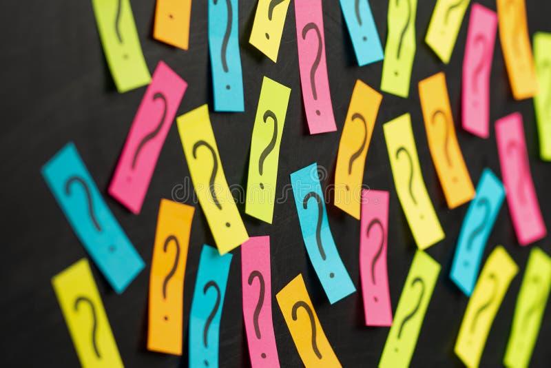 Teveel vragen Stapel van kleurrijke document nota's met vraagtekens close-up stock afbeelding