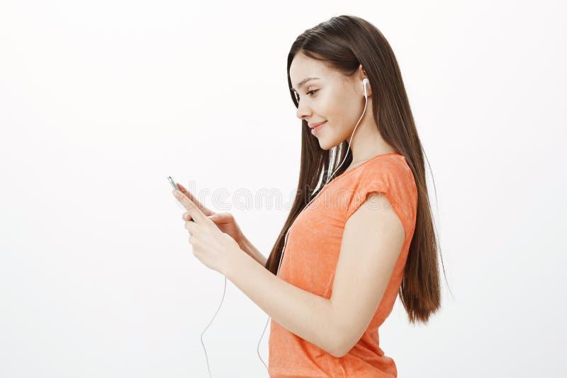 Tevreden actief meisje klaar voor ochtendjogging Mooi vrolijk meisje die zich in profiel over grijze achtergrond bevinden stock fotografie