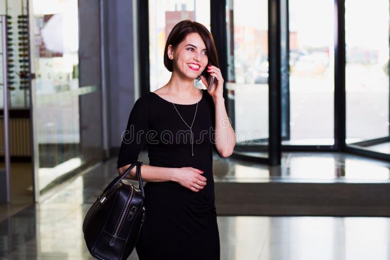 Tevreden bedrijfsdame in Winkelcomplex, die op de telefoon spreken royalty-vrije stock fotografie