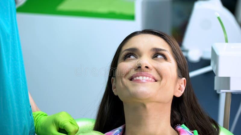 Tevreden cliënt na regelmatig tandonderzoek van mondholte, gezonde tanden stock afbeeldingen