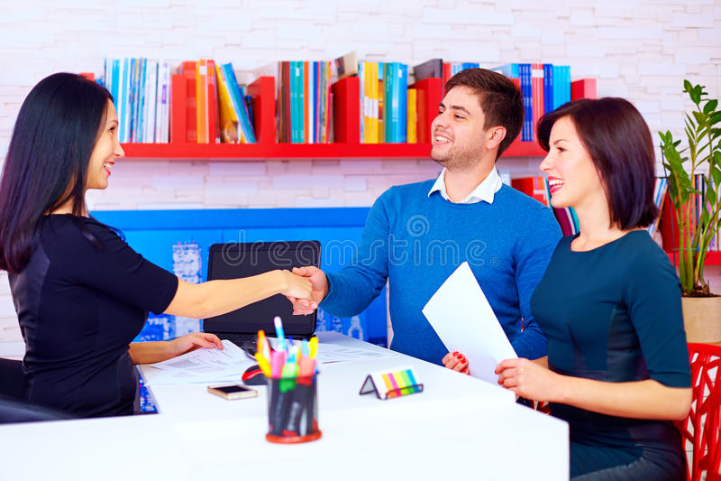 Tevreden cliënten, paar na succesvolle bedrijfsonderhandelingen in bureau stock foto