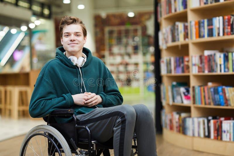 Tevreden gehandicapte student in bibliotheek stock foto's