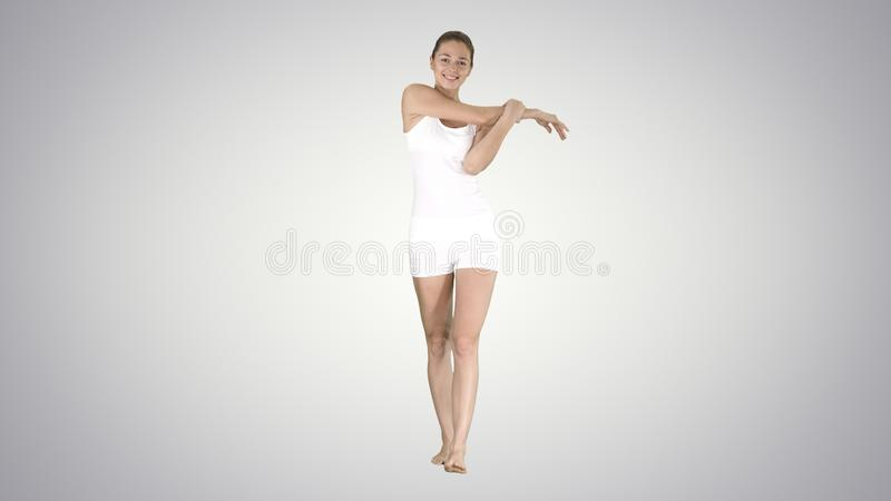 Tevreden gelukkige jonge vrouw die haar wapens uitrekken terwijl het lopen op gradiëntachtergrond stock foto
