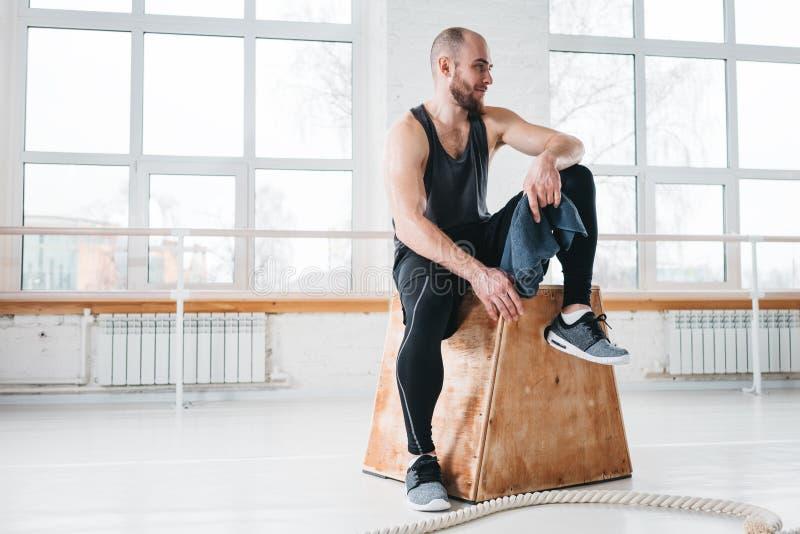 Tevreden geschikte atleet die na intense dwars het werkzitting rusten in traininggymnastiek royalty-vrije stock fotografie
