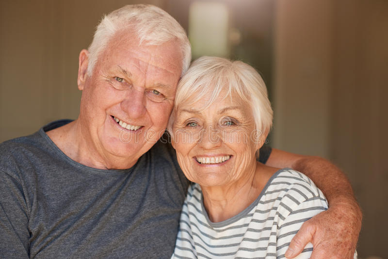 Tevreden hoger en paar die samen thuis glimlachen zitten stock afbeeldingen