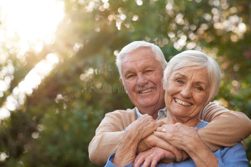 Tevreden hoger paar die gelukkig in openlucht samen glimlachen stock foto