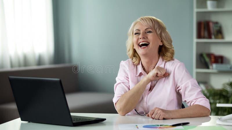 Tevreden hoger wijfje die voor computer, freelance het werkvoltooiing glimlachen stock afbeeldingen