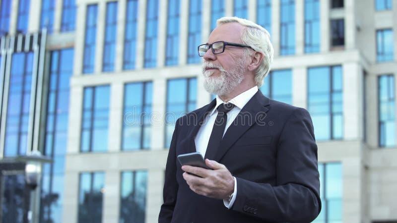 Tevreden hogere in hand smartphone van de zakenmanholding, gelukkige bedrijfdirecteur stock foto's