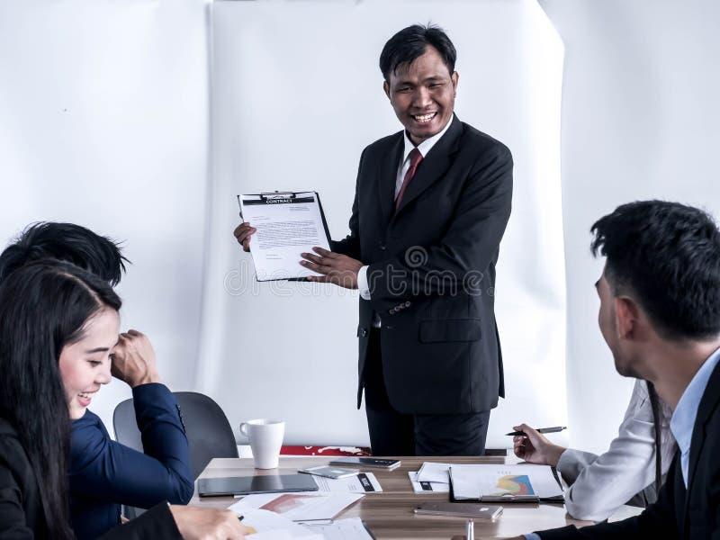 Tevreden hogere zakenman het delen van ideeën door whiteboard met partners bij presentatie stock afbeelding