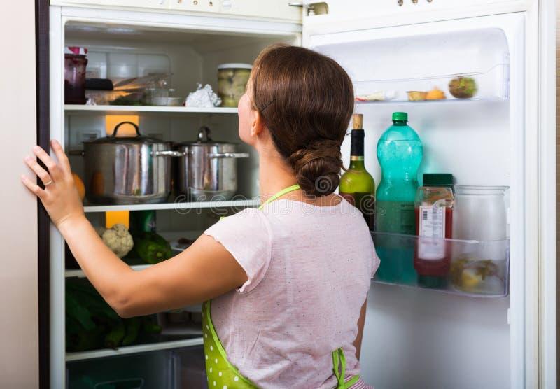 Tevreden huisvrouwen dichtbij gevuld koelkast stock foto's