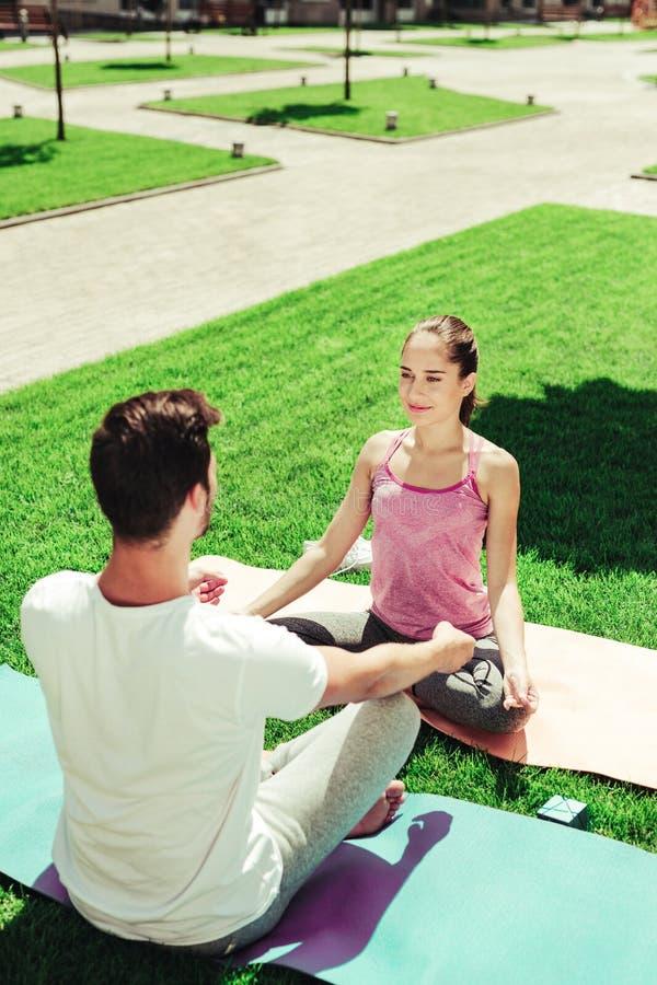 Tevreden jong houdend van paar die yoga samen doen stock fotografie