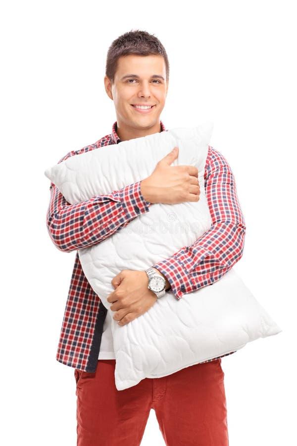 Tevreden jonge mens die een wit hoofdkussen koesteren royalty-vrije stock foto