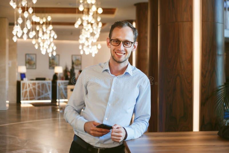 Tevreden jonge succesvolle zakenman ontwikkelaar houdt telefoon stock afbeeldingen