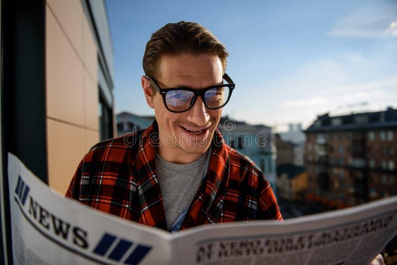 Tevreden kerel die de krant buiten lezen stock fotografie