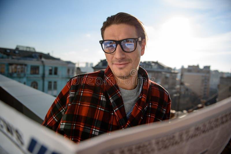 Tevreden kerel die zich op het balkon met krant bevinden royalty-vrije stock fotografie