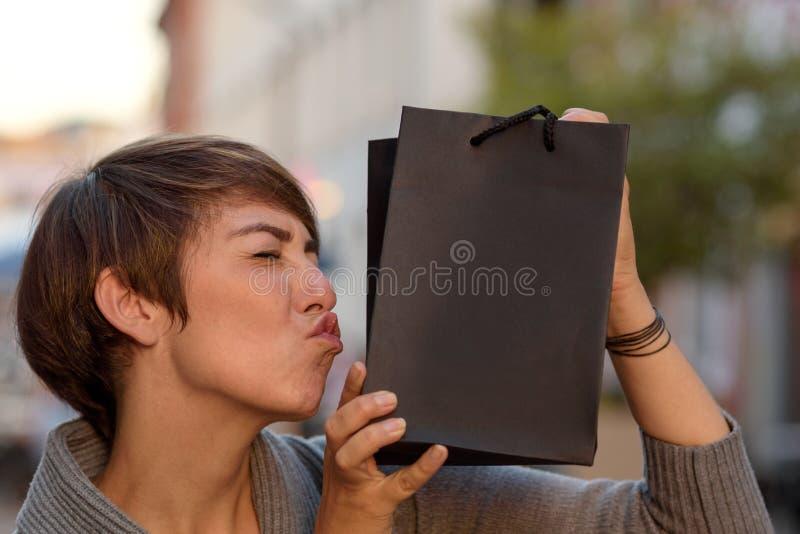 Tevreden klant die haar boutiquezak kussen stock afbeeldingen