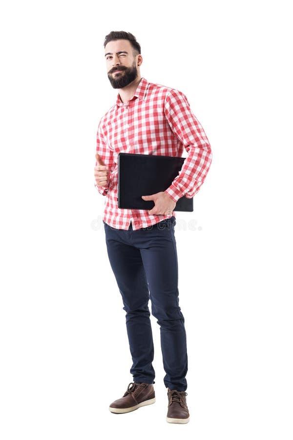 Tevreden knipogende gebaarde bedrijfsmens met laptop onder de duim van de wapenholding op gebaar stock foto