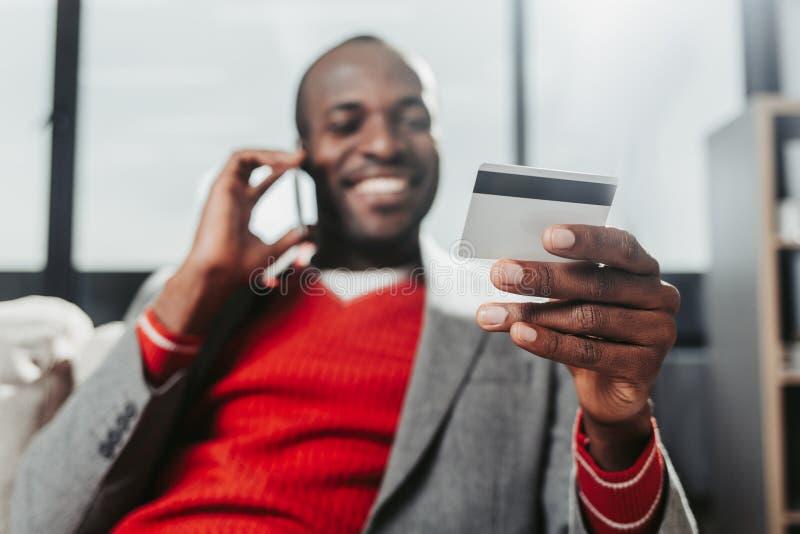 Tevreden mannetje met bankkaart die door smartphone spreken stock foto's