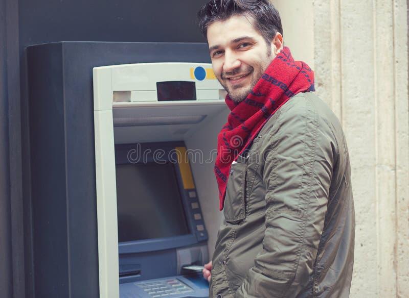 Tevreden mens die ATM-machine buiten met behulp van royalty-vrije stock foto's