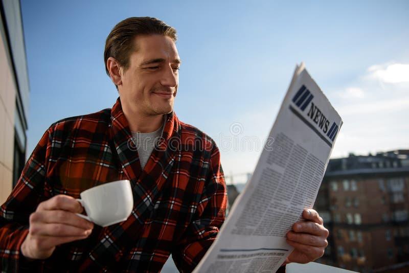 Tevreden mens die door het dagboek op het balkon kijken stock fotografie