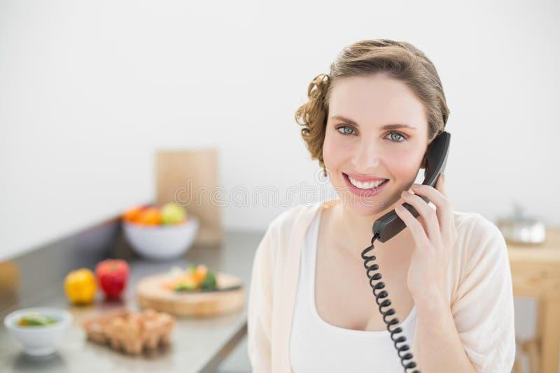 Tevreden mooie vrouw die in haar keuken met een telefoon telefoneren stock foto's