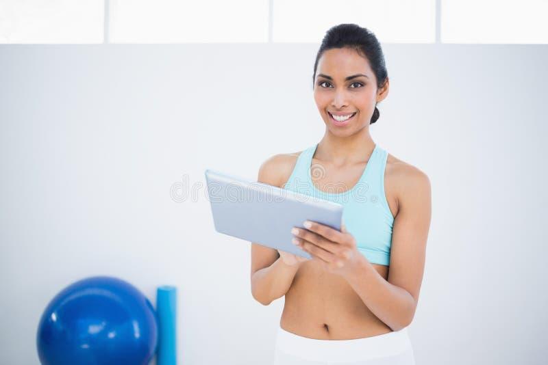 Tevreden mooie vrouw die in sportkleding haar tablet houden royalty-vrije stock afbeeldingen