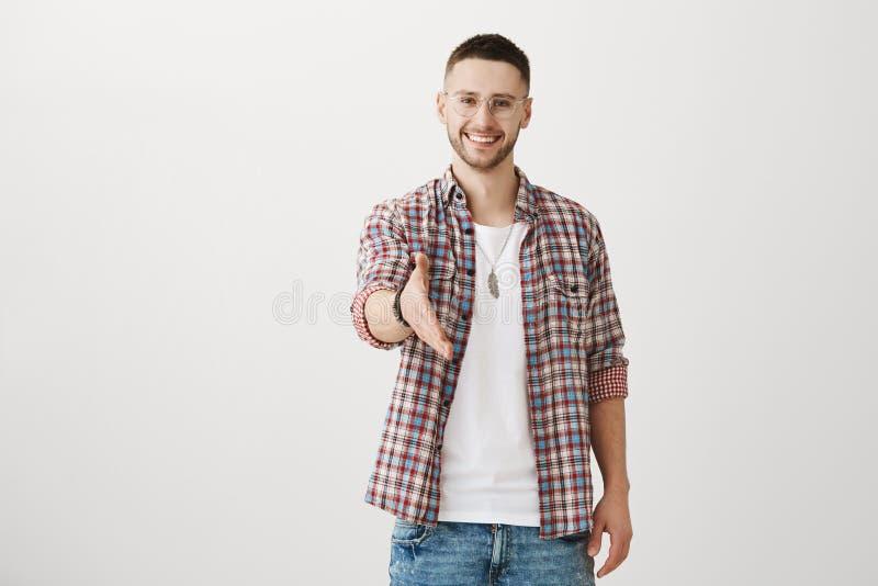 Tevreden om dergelijke persoon als u te ontmoeten Knappe ongeschoren mannelijke student in eyewear trekkende hand naar camera, di stock fotografie