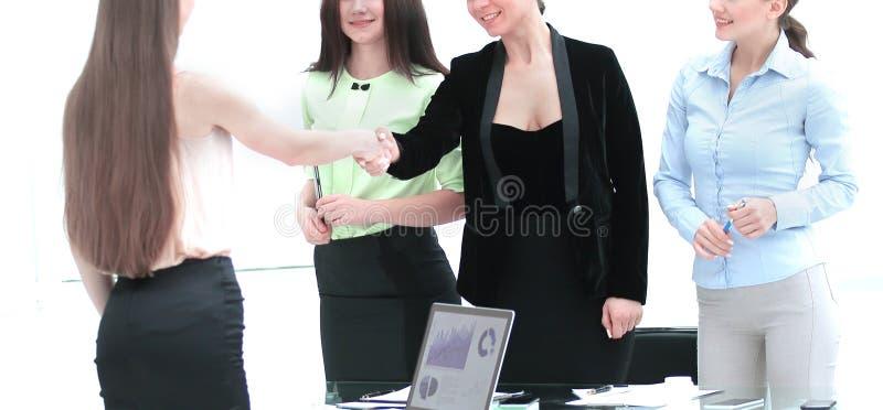 Tevreden oudere vrouw en jong managerhandenschudden na het ondertekenen van contract in bureau royalty-vrije stock foto