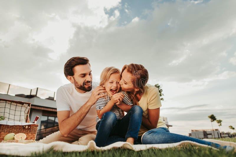 Tevreden paar met blij jong geitje tijdens picknick royalty-vrije stock fotografie