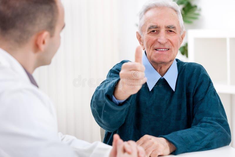 Tevreden patiënt bij arts stock afbeelding