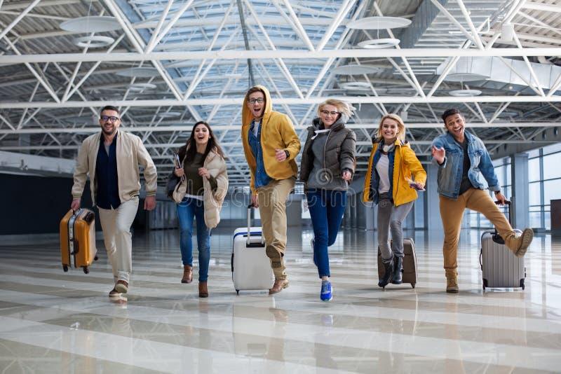 Tevreden reizigers die met bagage in de eindzaal lopen stock afbeelding