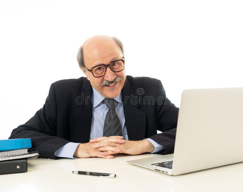 Tevreden rijpe bedrijfsmens die in zijn jaren '60 aan laptop werken zeker van succes stock afbeeldingen