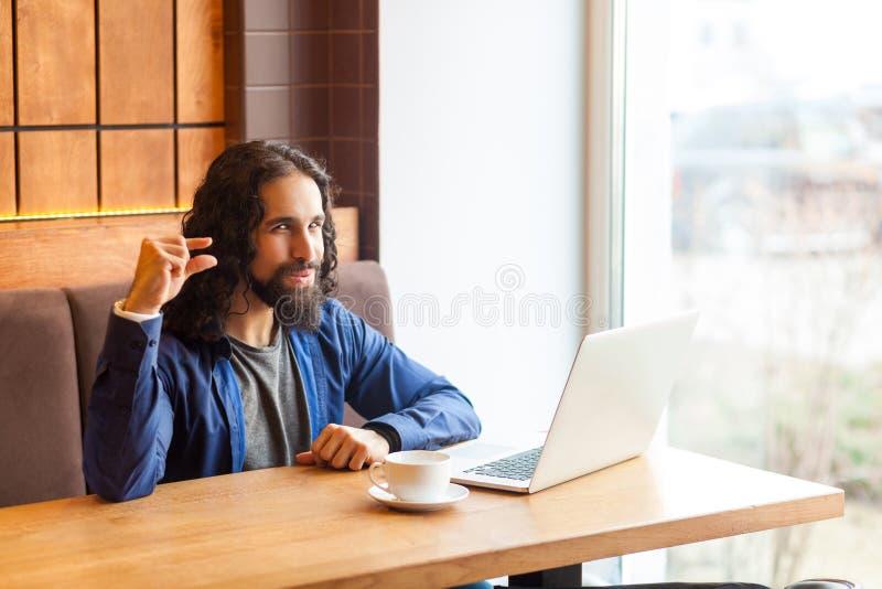 Tevreden snuifje! Portret die van de sluwe jonge volwassen mens freelancer in toevallige stijlzitting in koffie met laptop, camer royalty-vrije stock fotografie