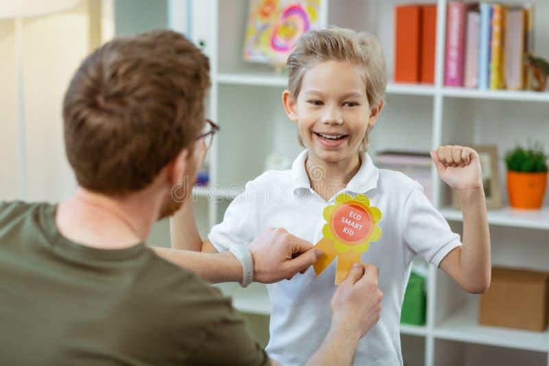 Tevreden trotse jongen die gelukkig met zijn beloning zijn royalty-vrije stock fotografie