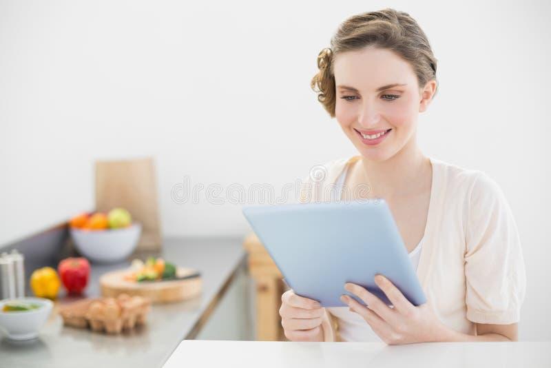 Tevreden vreedzame vrouw die haar tabletzitting in haar keuken gebruiken royalty-vrije stock afbeelding
