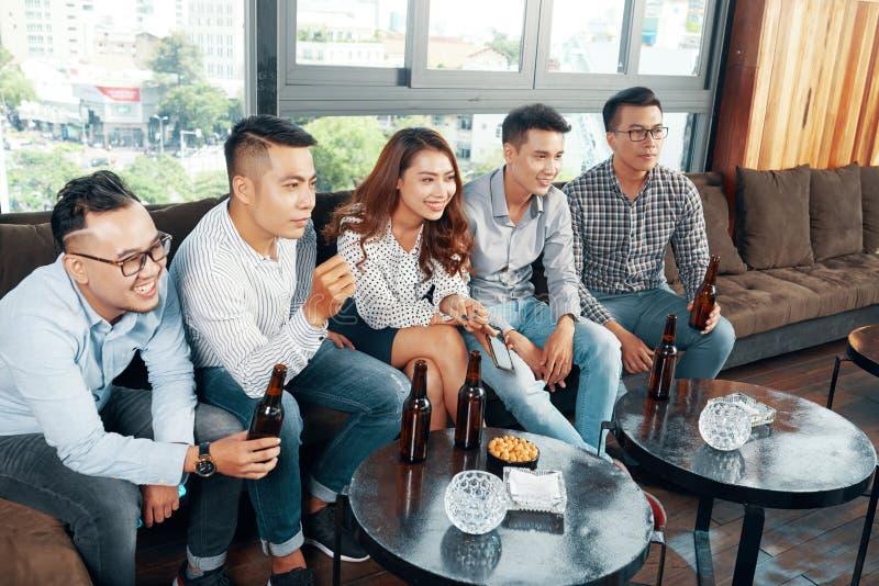 Tevreden vrienden die met bier op TV letten royalty-vrije stock afbeeldingen